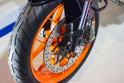 Detail Motorcycle wheel in black and orange with ABS brakes part of the motorcycle.