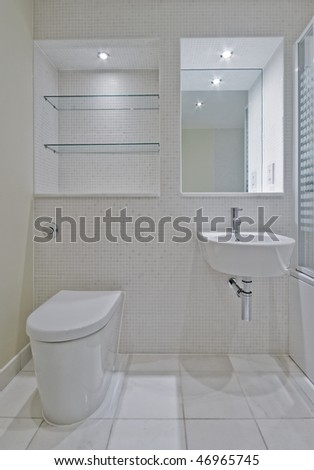 detail of a bathroom with white ceramic suite and mosaic tiles