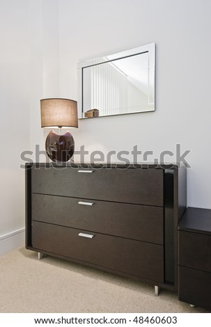 detail of a bedroom furniture in mahogany with night lamp