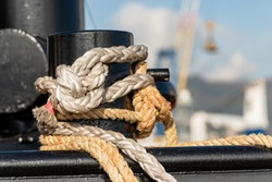 Detail of a black mooring bollard with ropes or hawsers on the deck of a ship moored in the port