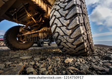 Detail of a black offroad tire and differential on underside of an offroad truck vehicle, built for heavy rides and unpaved roads #1214750917