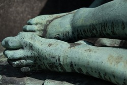 Detail of a bronze statue of the dead Christ, marks from the nails in his feet. Medieval sculpture of a dead Jesus after the crucifixion in a local churchyard in Prague.