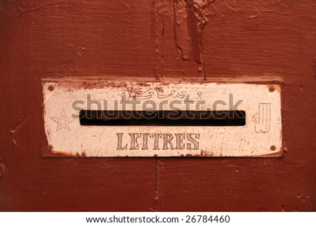 "Detail of a brown door with a mailbox with in arabic and fench language written ""letters""  - stock photo"