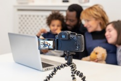 detail of a camcorder in operation while filming a mixed-race family, parents and children who use modern technology to film themselves and use it for their blog and social network, vlogger family