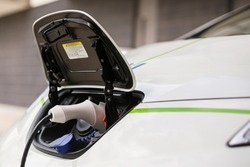 detail of a charging connector of a white electric car, while charging from a charging station