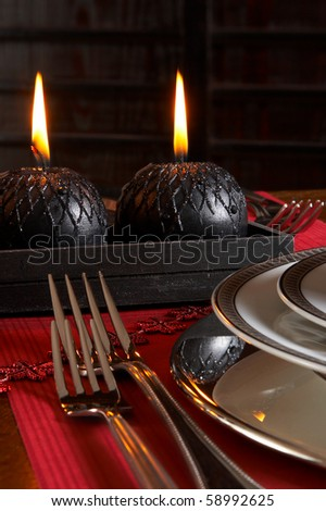 Detail of a christmas dinner table with red napkins and black candles