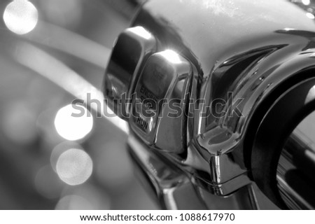 Detail of a classic American motorcycle engine kill switch. Chrome details and black rubber details. Close up of motorbike throttle outside, chrome reflecting in the hot sun. Classic bike. #1088617970