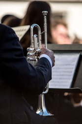 Detail of a classic silver trumpet in an orchestra. Sheet of musical notes in the background out of focus.
