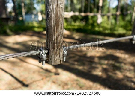 Detail of a constructions in adventure park. Wooden parts connected to each other by steel cable. Strong connections to stand active usage of the outdoor sporting goods. Aegviidu, Estonia #1482927680