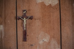 Detail of a Crucifix in an abandoned building on a wooden wall