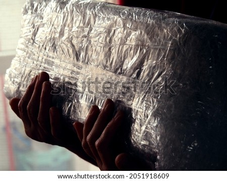 Detail of a delivery box covered in bubble folie being held in hands  Stock fotó ©