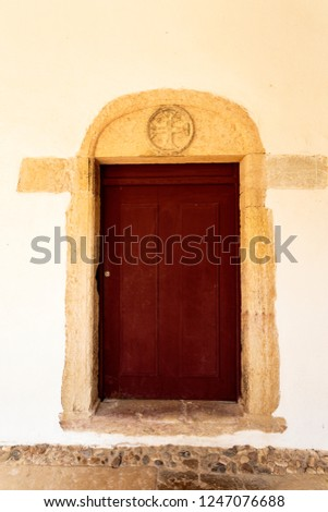 Detail of a door with the Cross of Christ in the architrave, symbol of the Order of Christ, in the Micha Cloister of the Convent of Christ, Tomar, Portugal