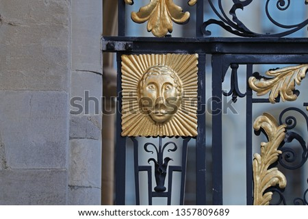 Detail of a face and ornate ironwork on the side entrance gate to All Souls College Oxford one of the constituent colleges of the university and only open to graduates