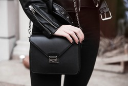 detail of a fashionable woman wearing short leather jacket,black purse,watches,black jeans.Unrecognizable model wearing casual outfit and holding purse.Street, copy space.Fall outfit.