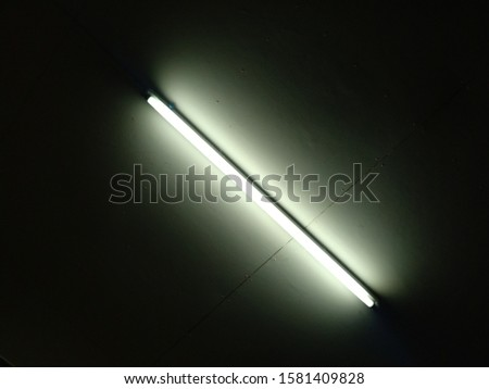 Detail of a fluorescent light tube on a wall. fluorescent light tube  space for any design. Electric lamp and energy power concept.