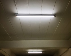 Detail of a fluorescent light tube on a wall. fluorescent light tube with copy space for any design. Electric lamp and energy power concept.