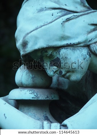 Detail of a gravestone statue showing the face of a sorrow woman