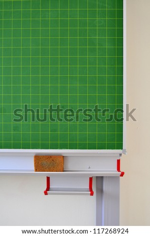 Detail of a green blackboard with sponge in a school