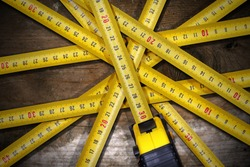 Detail of a group of tape measures on a wooden table with dark shadows