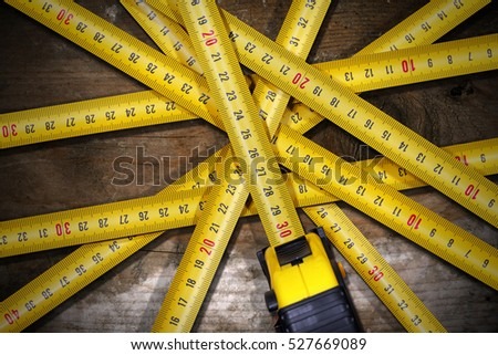 Detail of a group of tape measures on a wooden table with dark shadows #527669089