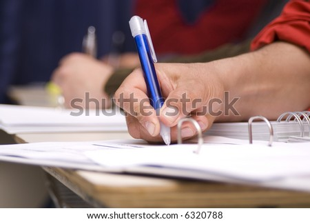 detail of a hand of man with red shirt  writing on a notebook with a blue pencil  and  blurred background