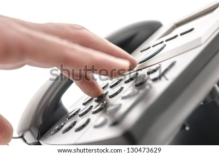 Detail of a hand pressing a button on a telephone keypad. With selective focus.