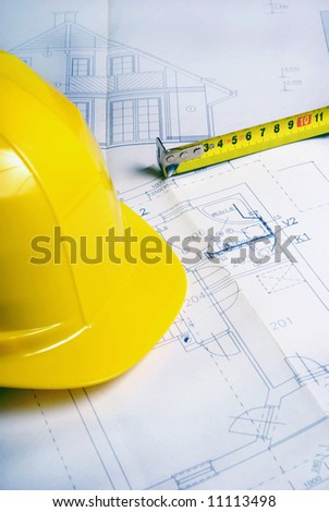 detail of a hard hat, measuring tape and construction plan for a house