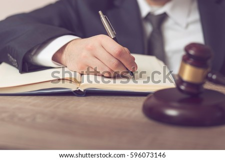 Detail of a judge sitting at his desk, studying new laws and legislation and writing notes. Selective focus