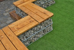 Detail of a low gabion wall with a wood on the top for a use as a bench