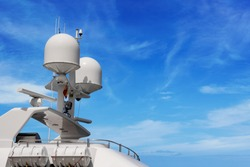 Detail of a luxury white yacht with navigation equipment, radar and antennas on blue sky, superstructure