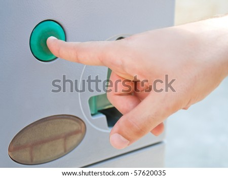 Detail of a male hand pressing a green button.