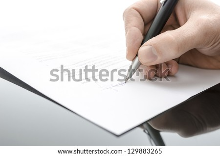 Detail of a male hand signing a contract on a black table.