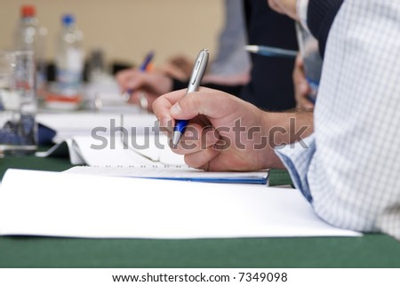 detail of a man hand  writing on a notebook with a blue pencil  and  blurred background