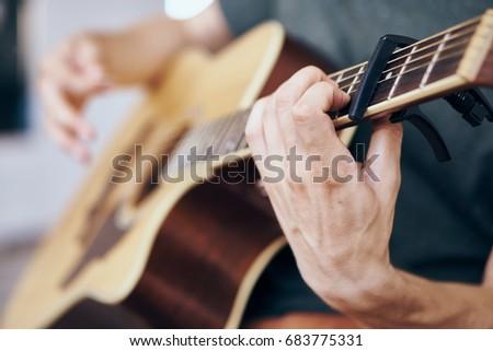 Detail of a man playing guitar