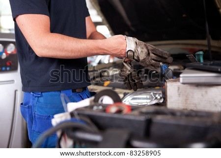 Detail of a mechanic putting on dirty work gloves
