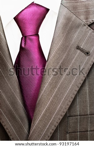Detail of a men's striped business suit.Pink tie and a shirt