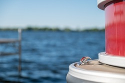 Detail of a metal cleat on the front of a red pontoon boat with a dock, lake and horizon in the background, with selective focus and narrow depth of field.