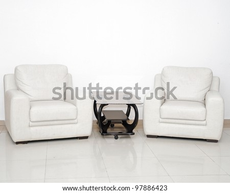 Detail of a modern living room with white armchair and glass coffee table - stock photo
