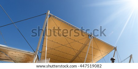 Detail of a modern tensile structure, membrane fabric roof with poles and steel cables, on a blue clear sky with sun rays #447519082