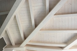 Detail of a modern wooden roof. All the beams are painted in a soft white