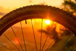 Detail of a mountain bike wheel at sunset. Close-up of bicycle tire. Enduro, downhill, cross country. Space for Text.