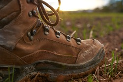 Detail of a mountain boot in a sunny day of trekking in the countryside