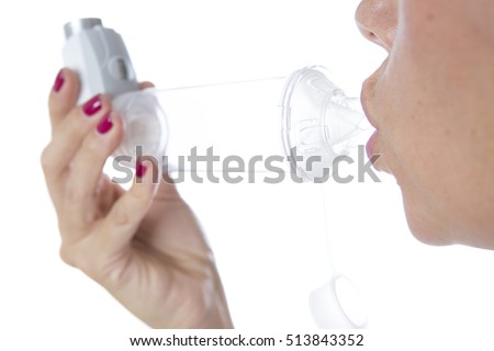 Detail of a mouth is inhaling the medicament from the pressurized cartridge inhaler placed on an inhalation chamber - Isolated on a white background Imagine de stoc ©
