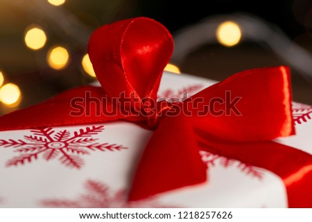 Detail of a nicely wrapped Christmas present and Christmas lights on a rustic wooden table. Selective focus. Selective focus #1218257626
