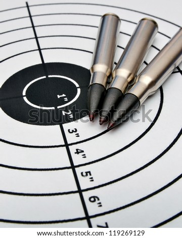Detail of a paper target and three bullets