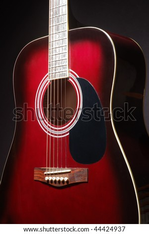 Detail of a red guitar on black background