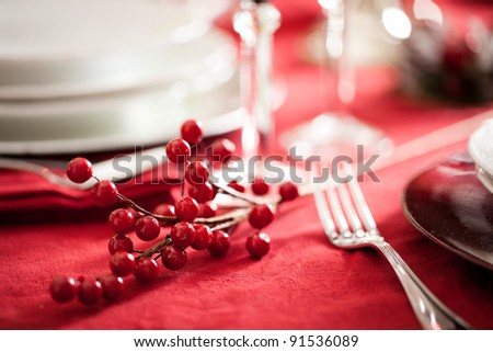 detail of a red holly berry decoration on a festive table setting