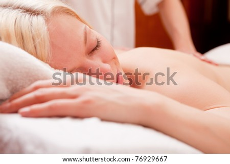 Detail of a relaxed woman receiving a back massage at a spa