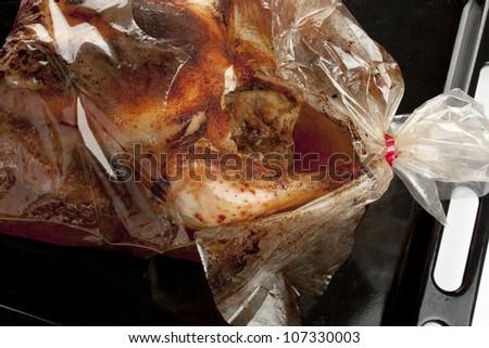 detail of a roast chicken into a broken oven bag