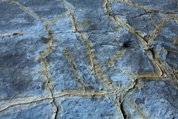Detail of a rock with variants of blue and yellow patterns.Rock full of smooth traces resulting from the erosive effect of sea. Close up rock. Natural texture and colorful.
